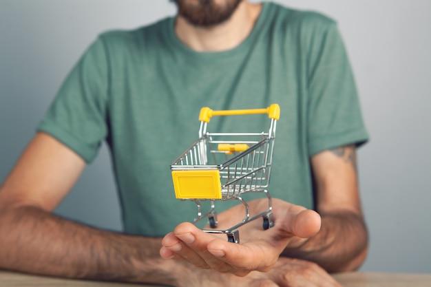 男は手にカートを持っています。灰色の背景のショッピングコンセプト