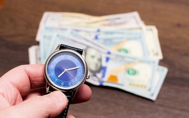 男は米ドルを背景に時計を握る