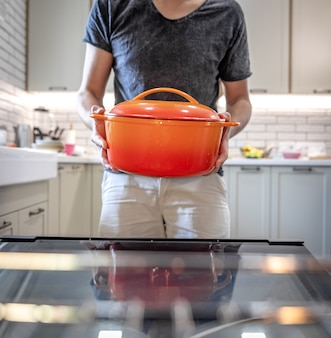 한 남자가 접시를 오븐에 넣기 전에 손에 접시를 들고 있습니다.