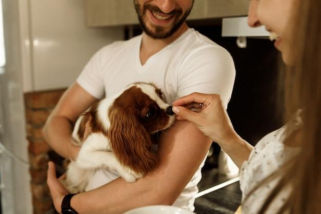 남자는 개를 팔에 안고 여자는 개를 먹이