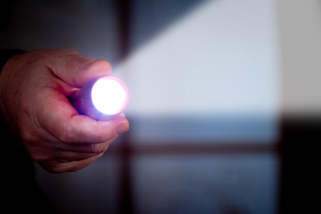 남자는 어두운 방에서 손전등을 보유하고 있습니다. 다른 사람의 집에 침투