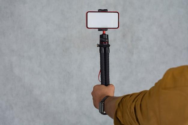 한 남자가 흰색 화면이 있는 스마트폰 모형으로 유연한 삼각대를 들고 있습니다.
