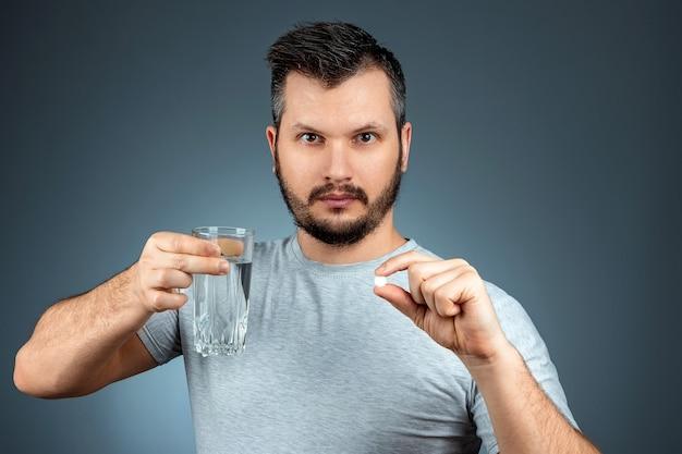 男はコップ1杯の水と錠剤を持ち、薬、治療、灰色の壁を取っています。医療テーマ、ビタミン、ヘルスケア。