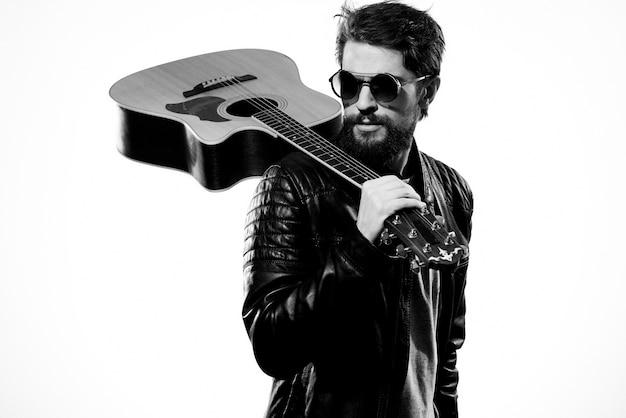 男は彼の手でギターを持っています黒い革のジャケット暗い眼鏡音楽パフォーマンス明るい背景。