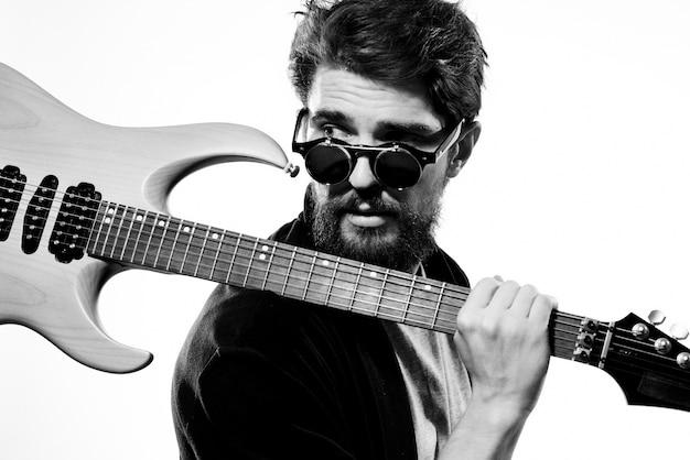 Мужчина держит гитару в руках черная кожаная куртка темные очки музыкальное представление светлое пространство