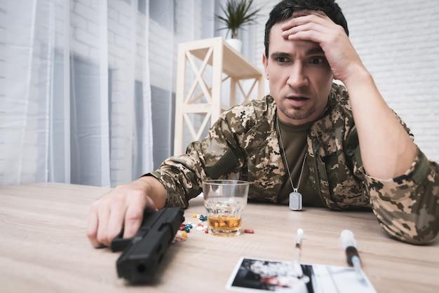 Мужчина держит пистолет в руке и держится за голову.