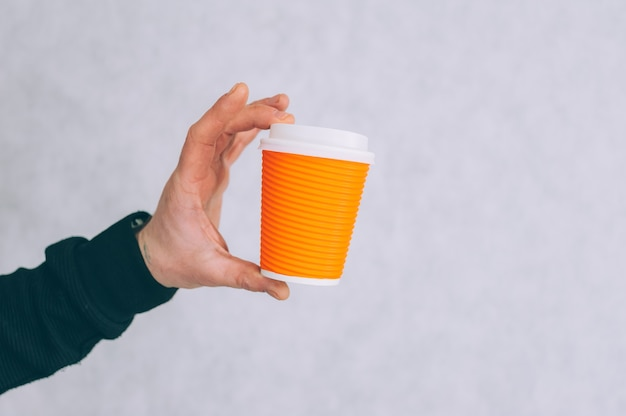 男性がライトにコーヒーと紅茶の紙コップのモックアップを持っています。