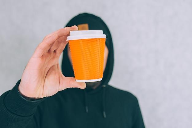 한 남자가 커피와 차를위한 종이컵 모형을 조명에 들고 있습니다.