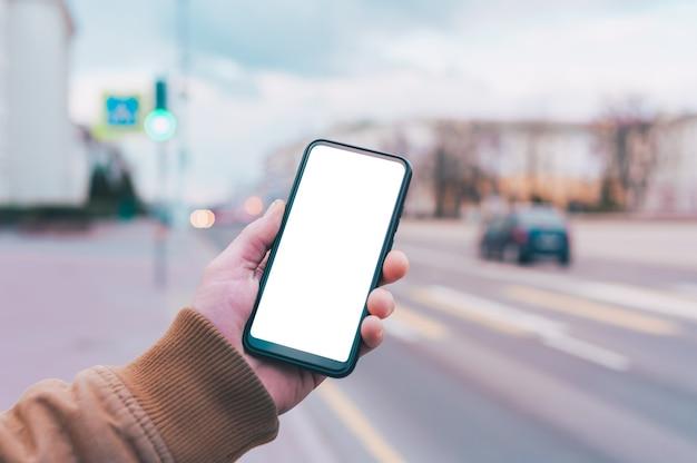 男は、道路の背景に白い画面でスマートフォンのモックアップを保持しています。