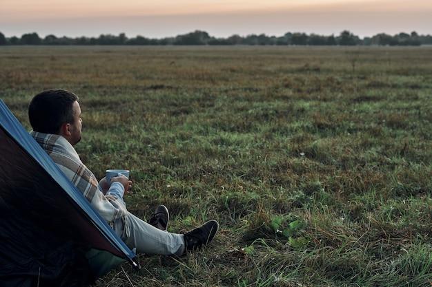 男はマグカップを手に持って夜明けを見ます。旅行者、日の出。