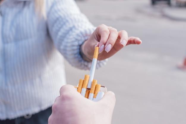 한 남자가 담배 한 갑을 손에 들고 여자에게 담배를 준다.