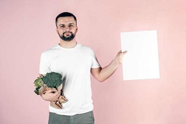 Мужчина держит в руках бумажный пакет с овощами, копией пространства.