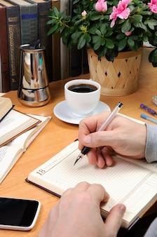 한 남자가 펜을 들고 책으로 둘러싸인 사무실 책상 위의 공책에 메모를 한다