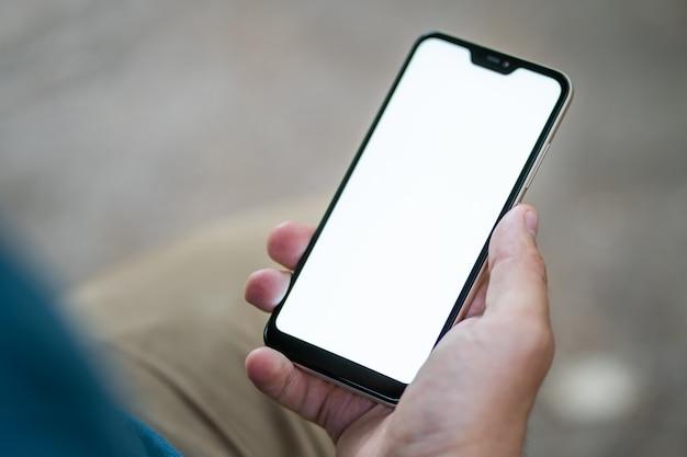男は彼の手のクローズアップで白い画面で携帯電話を持っています。コピースペース