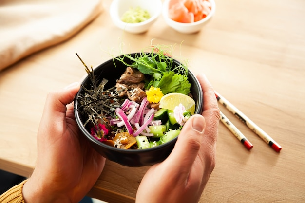 한 남자가 손에 쇠고기와 함께 포크 샐러드를 들고 있습니다. 재료 쇠고기 아시아 샐러드 개념