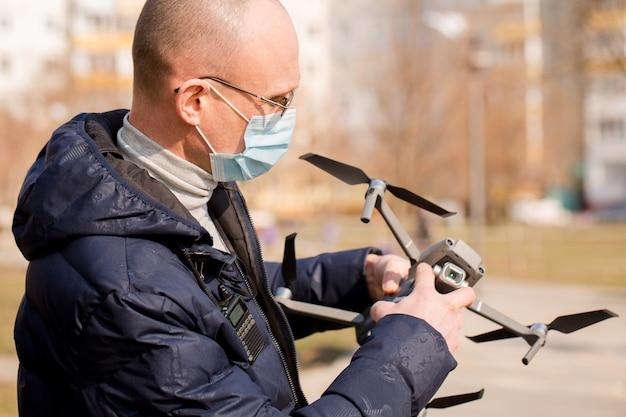男はquadrocopterとコントロールパネルを保持しています。