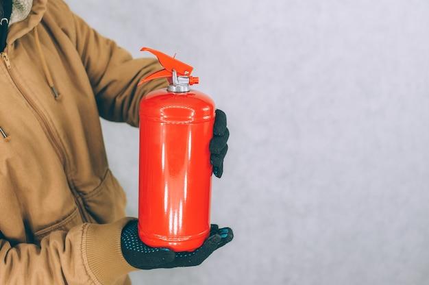 男は白い上に赤い消火器を手に持っています。