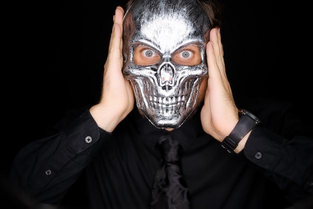 Мужчина держит перед собой маску-скелет, что