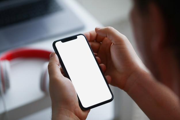 Мужчина держит смартфон, крупным планом рука с телефоном.