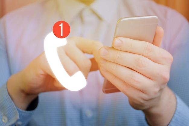 남자는 자신의 손으로 스마트 폰을 가지고 있으며, 전경에는 부재중 전화에 대한 표시가있는 핸드셋 아이콘이 있습니다. 피드백