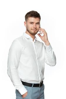 Мужчина держит в руках телефон и звонит. портрет молодого парня в белой рубашке изолированной на белой предпосылке.