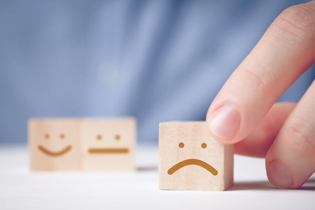 Мужчина держит деревянный кубик с недовольным лицом на нейтральной и позитивной. для оценки действия или ресурса.