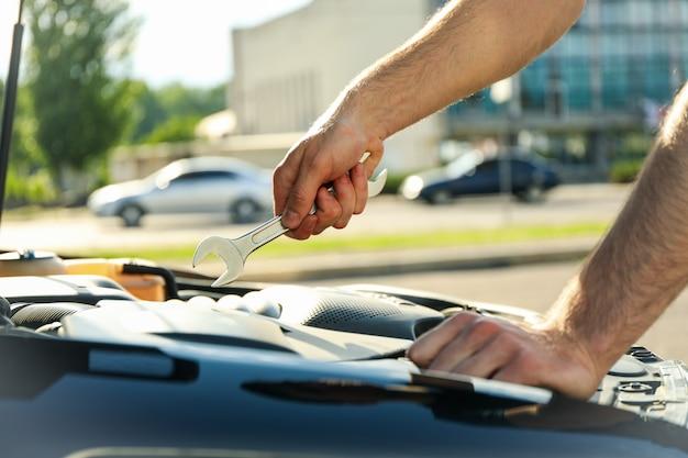 Мужчина держит гаечный ключ над двигателем автомобиля. автоинспекция