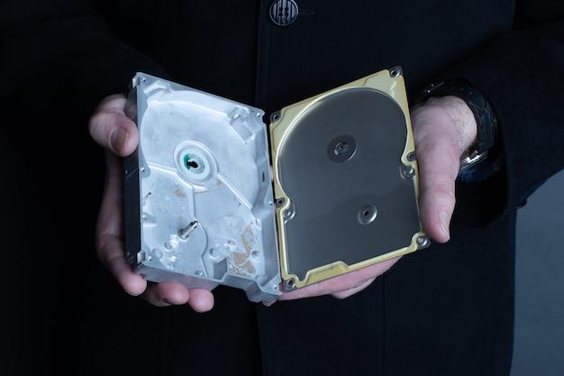 Мужчина держит в руках пустой открытый жесткий диск. кража личных данных или концепция корпоративной тайны.
