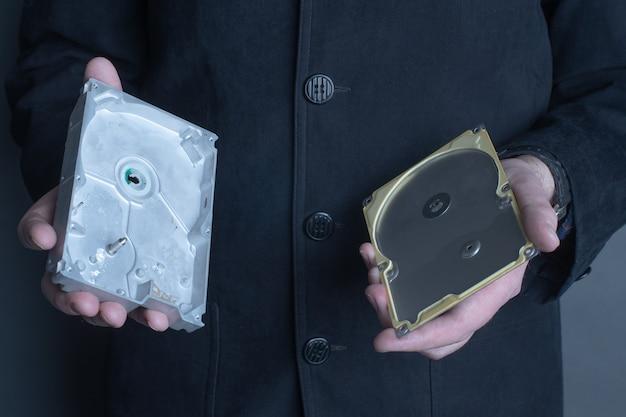 Мужчина держит в руках пустой открытый жесткий диск