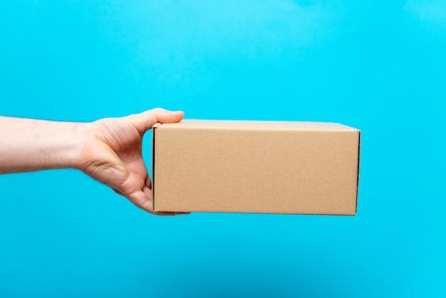 男は青い背景に彼の手でボックスを保持します。商品のサービス提供。市の配達サービス。