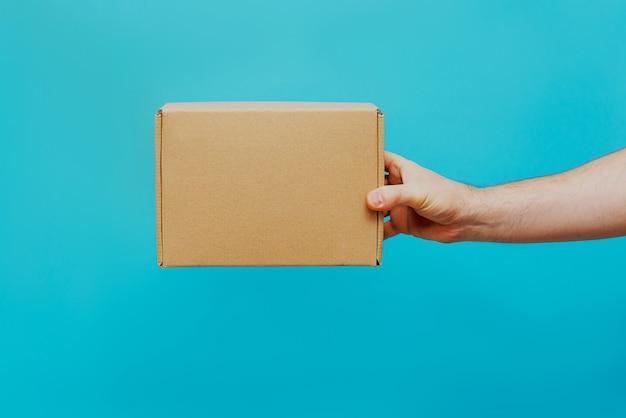 남자는 파란색 배경에 그의 손에 상자를 보유하고 있습니다. 상품의 서비스 제공. 도시 배달 서비스.