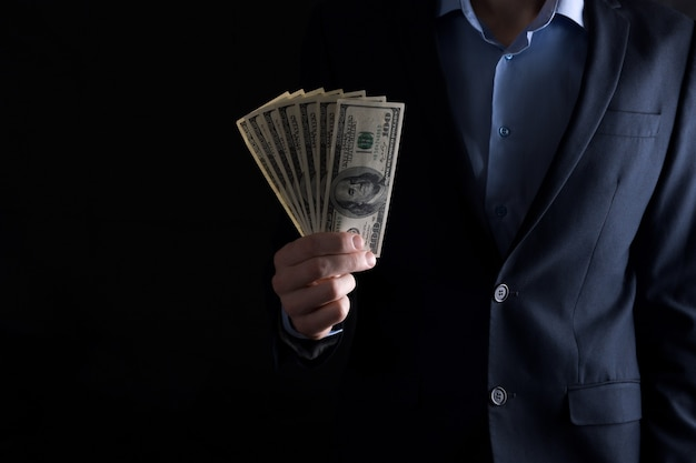 Мужчина держит в руках доллары. мужчина считает доллары.