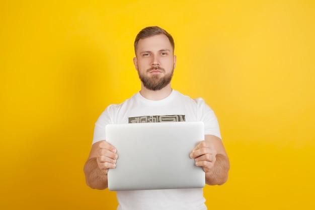男は黄色の背景にラップトップを持って彼の前に手を伸ばしている。新しい現代の技術、ガジェット、コンピューターでの作業の概念。
