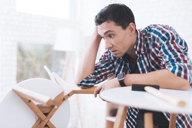 Мужчина держит голову и смотрит на сломанный стул.