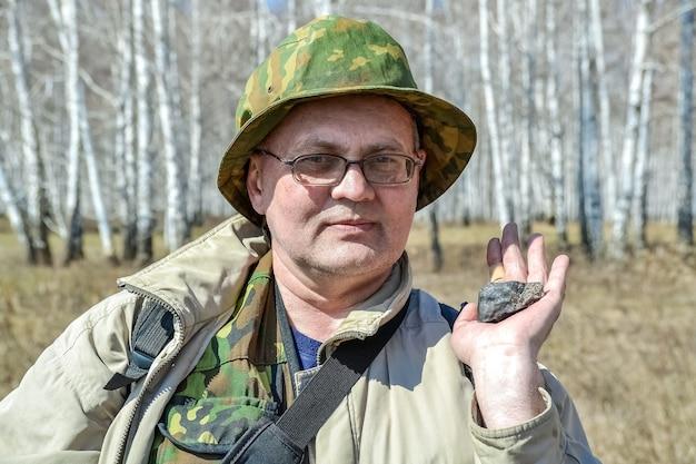 한 남자가 2013년 봄에 발견된 첼랴빈스크 운석 조각을 손에 들고 있다