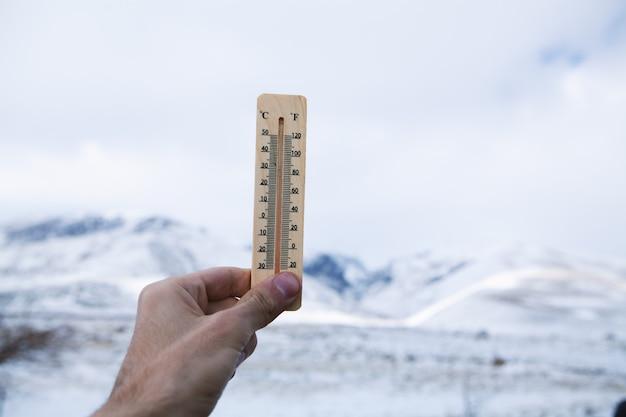 남자는 그의 손에 온도를 보여주는 눈 온도계를 보유