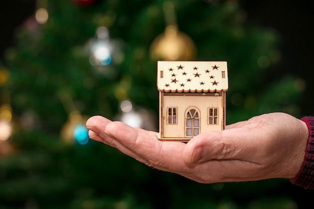 男は、クリスマス ツリーの近くの木のおもちゃの家を手に持っています。新年の贈り物としての家