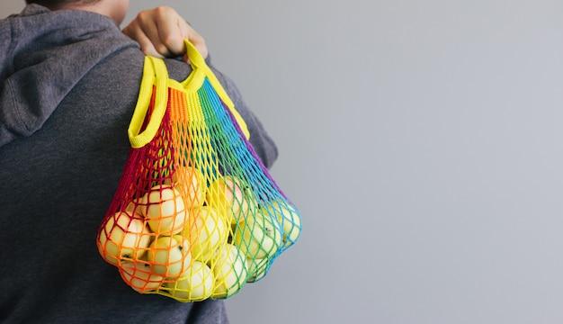 Мужчина держит в руках многоразовую хлопковую авоську для покупок, разноцветную радугу с зелеными яблоками внутри. серый фон. концепция нулевых отходов