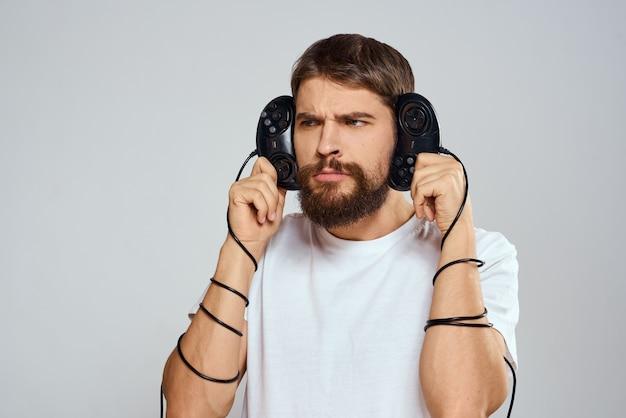남자는 그의 손에 레저 기술 라이프 스타일 흰색 티셔츠를 재생하는 두 개의 조이스틱을 보유하고 있습니다. 고품질 사진
