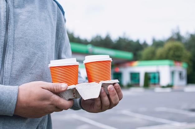 한 남자가 주유소에서 손에 커피 두 잔을 들고있다.