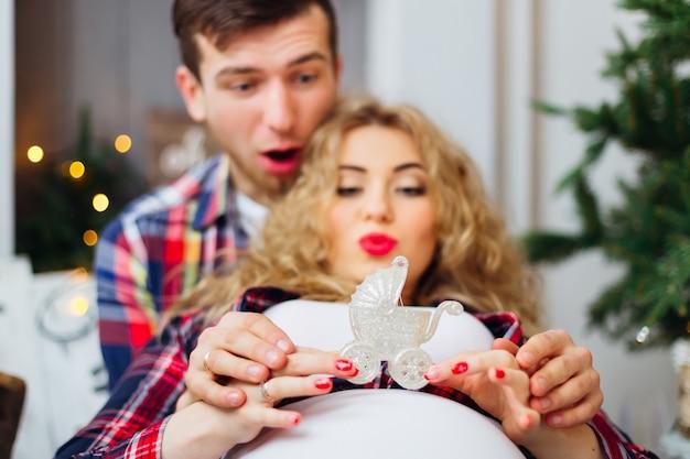男が妊娠中の妻を抱きしめ、おもちゃのベビーカーを楽しんでいます