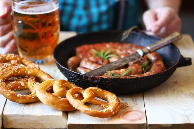 バーの男性がソーセージとプレッツェルをビールと一緒に食べます。オクトーバーフェストメニュー。