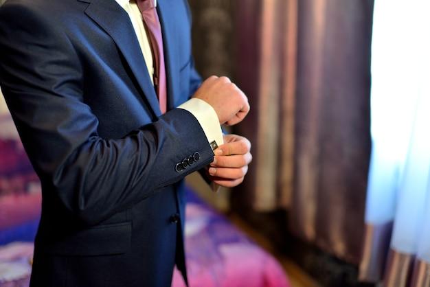 아름다운 양복을 입은 남자가 셔츠의 커프스 단추를 조정합니다