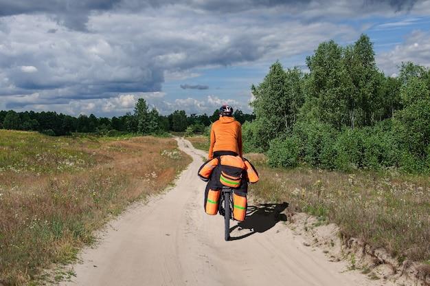 큰 자전거 배낭이 달린 자전거 유니폼을 입은 남자가 비포장 도로에서 산악 자전거를 타다.