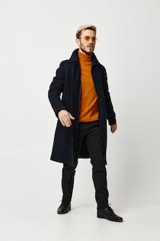 黒のジャケットとズボンとオレンジ色のセーターを着た男性がライトで横を向いています