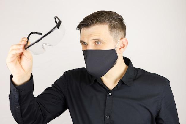 黒の保護マスクの男は、白い背景の上の医療眼鏡をのぞきます