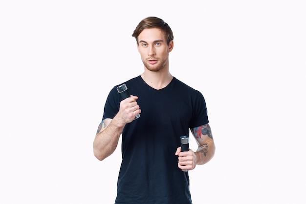 그의 손 스포츠 피트니스 모델에 아령과 검은 색 티셔츠에 남자