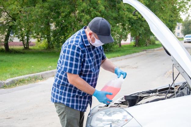 青い市松模様のシャツと青い医療用マスクを着た男性が、ボンネットを開けたまま車のそばに立っています。
