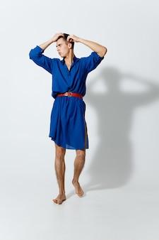 青いドレスを着た男性がゲイの手を頭の後ろで完全に成長させている
