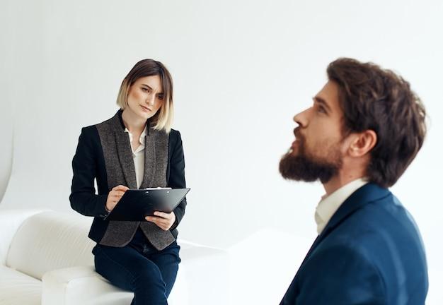 파란색 재킷을 입은 남자가 실내에서 정장을 입은 여자의 반대편에 앉아있다.